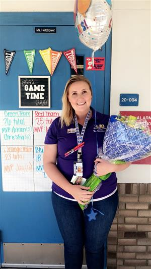 Ms. Holtzhower standing in front of her classroom door holding flowers