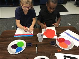 Afterschool students using supplies to paint