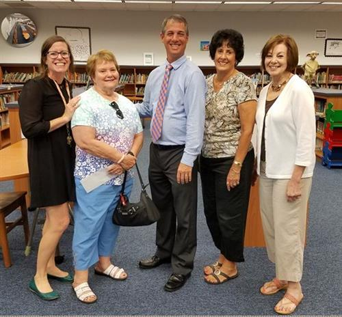 Ladies from the Jacaramba Island Book Club pictured with the principal and media specialist because they donated money to hel