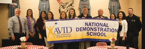 Administrators and staff hold up the AVID National Demonstration School on Validation Day