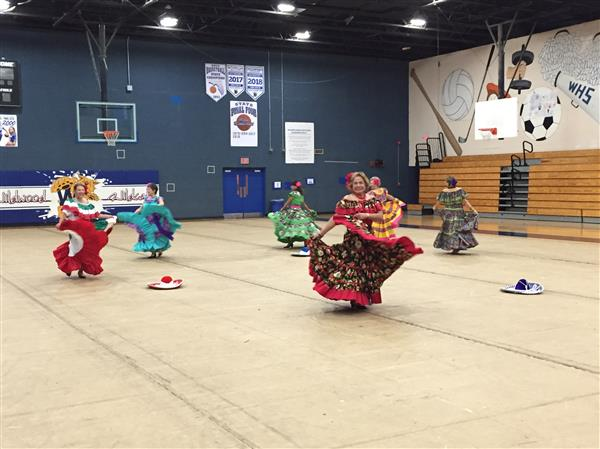 Six women are performing a Latin American dance in the gym.