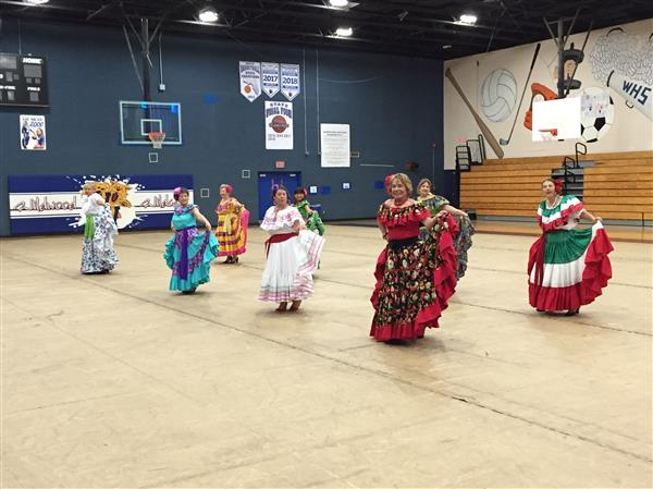 Eight women are performing a Latin American dance in the gym