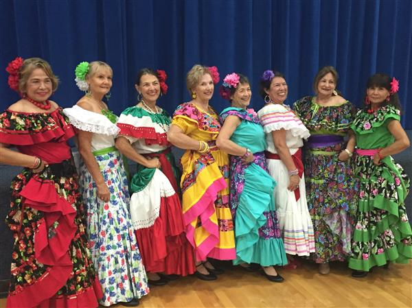 Eight women pose in Latin American costumes for a group picture.  They are smiling