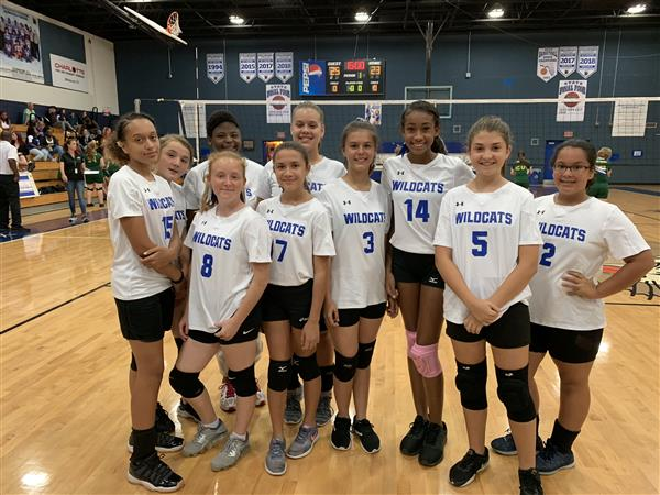 The 10 girls that are part of Varsity Middle School Team pose for a photo in front of the volleyball net.