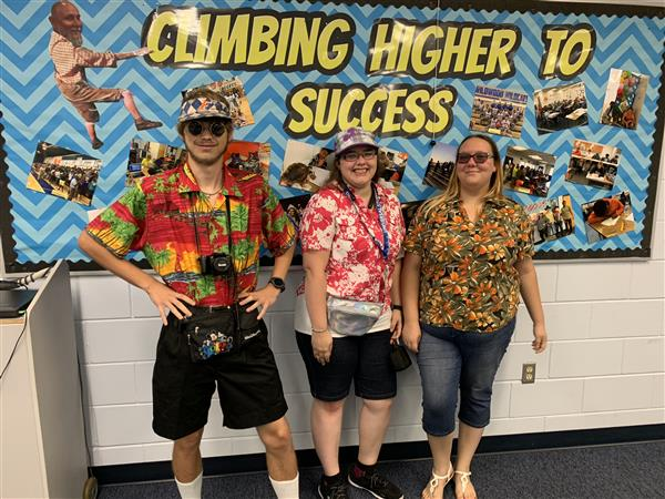 Three students dressed like tourists
