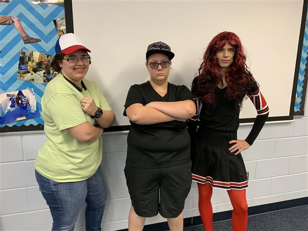 Two girls are dressed as boys, and one boy is dressed like a girl
