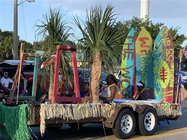 A parade float with palm trees and surf boards.  Some students are riding on the float.