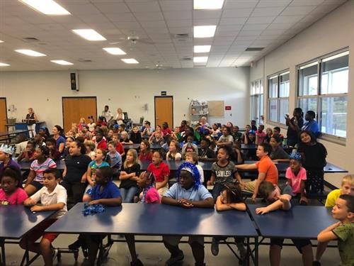 3rd Grade students sitting at tables in the lunch room during a pep rally
