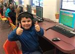 Kindergarten student giving thumbs up after writing his code