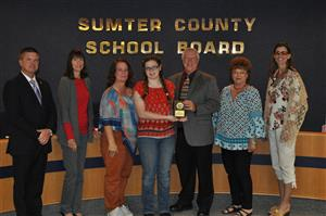 Picture of Rachel Story with Board Members presenting a plaque