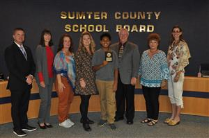 Picture of Mehki McCullough with Board Members presenting a plaque