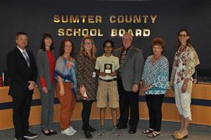 Picture of Noah Gerard with Board Members presenting a plaque