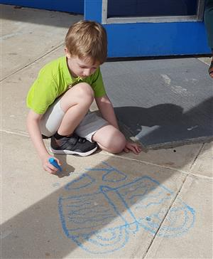 students writing on sidewalk with chalk for literacy week
