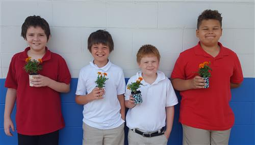 4 students with marigold flowers